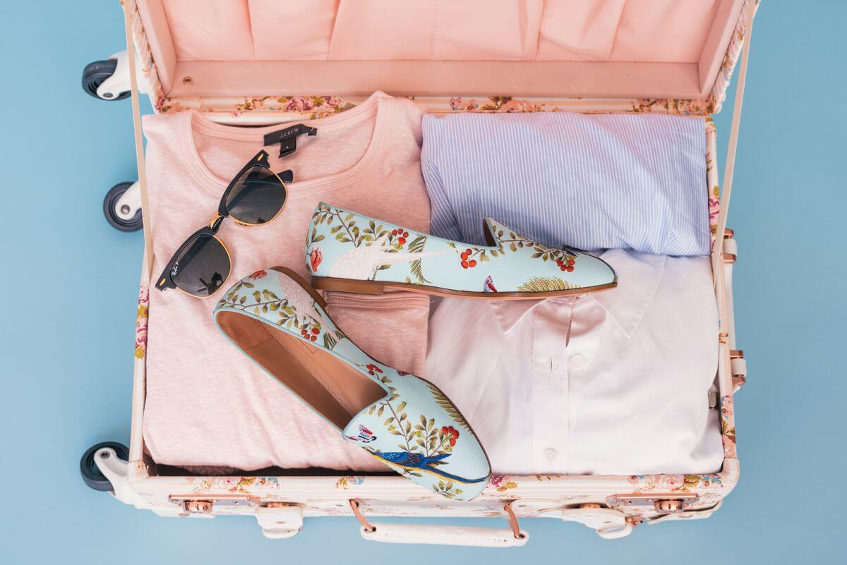 Open retro suitcase with shoes, sunglasses and clothes